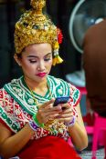 Travel photography:Girl in traditional Thai dress with mobile phone, Thailand