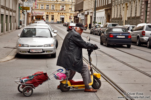 Man on a small scooter in Vienna