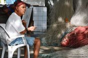 Travel photography:Copacabana fisherman mending his net, Brazil