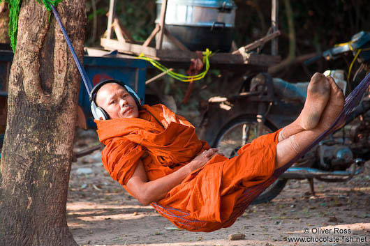 Buddhist monk with headphones near Angkor Thom