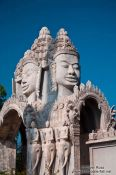 Travel photography:Giant faces above one of the entrance gates to the Vipassara Dhara Buddhist Centre near Odonk (Udong), Cambodia