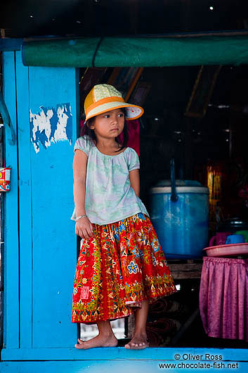 Small girl standing in a window frame near Tonle Sap lake