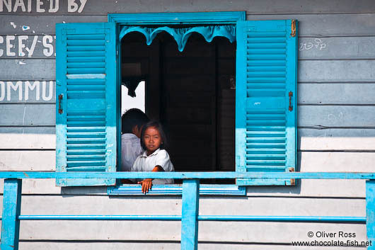 Girl looking out from her school`s window near Tonle Sap lake
