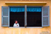 Travel photography:Girl looking out a window along a river near Battambang, Cambodia