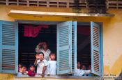 Travel photography:Kids waving out from their school window, Cambodia