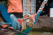 Travel photography:Man having a rest on his boat near Battambang, Cambodia