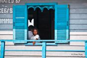 Travel photography:Girl looking out from her school`s window near Tonle Sap lake, Cambodia