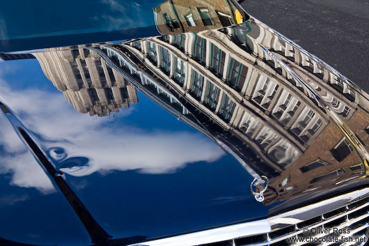 Montreal city buildings reflected on a car hood