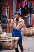 Travel photography:Woman carrying baskets in Lijiang, China