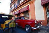 Travel photography:Classic car with a coco-taxi outside the Cigar Museum, Cuba