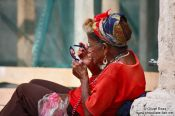 Travel photography:Old woman applying make-up on a street in Havana Vieja, Cuba