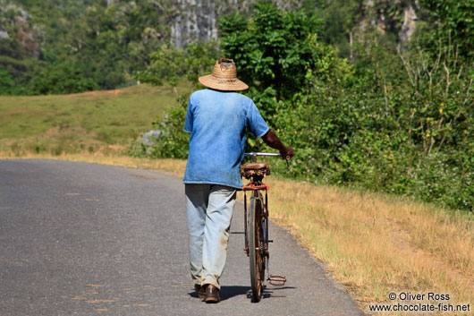 Man pushing his bike near Viñales