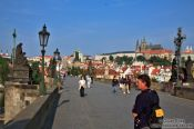 Travel photography:Tourists on the Charles Bridge with the Prague castle in the background, Czech Republic