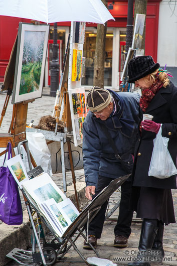 Passers-by browse through the art on offer in Paris´ Montmartre district