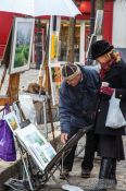 Travel photography:Passers-by browse through the art on offer in Paris´ Montmartre district, France