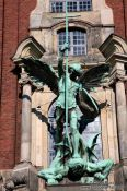 Travel photography:Bronze sculpture of the archangel Michael defeating the devil above the entrance portal of St. Michaelis church (Michel), Germany