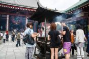 Travel photography:Visitors in Tokyo´s Senso-ji temple in Asakusa rub in smoke for good luck, Japan