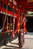 Travel photography:Two girls in Kimono pray at  Kyoto´s Inari shrine, Japan