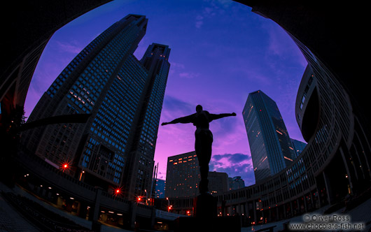 Statue with Tokyo Metropolitan Government Building in Shinjuku at sunset