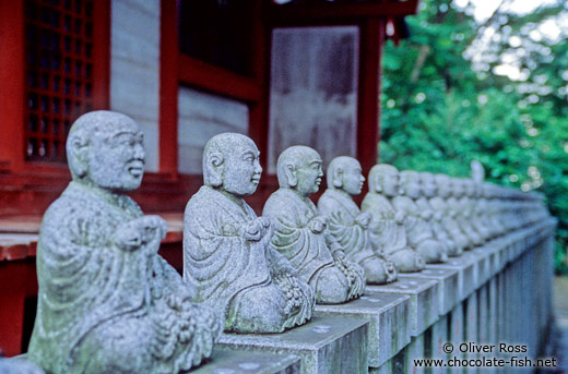 Row of little buddhas outside a forest shrine