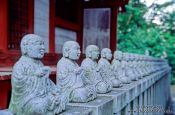 Travel photography:Row of little buddhas outside a forest shrine, Japan