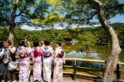 Travel photography:Girls in kimonos at the Golden Pavilion in Kyoto´s Kinkakuji temple, Japan