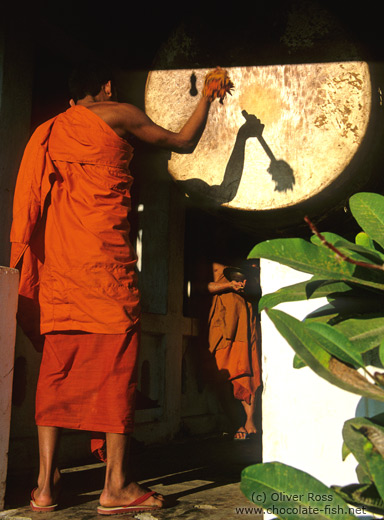 Buddhist monk novice performing the drumming ritual just before sunset