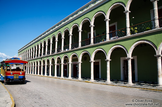 Colonnades along the main square in Campeche with tourist bus