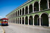 Travel photography:Colonnades along the main square in Campeche with tourist bus, Mexico