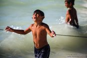 Travel photography:Boy in Celestun asking the arriving fishermen for some fish, Mexico