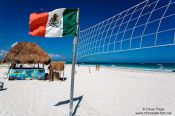 Travel photography:Volleyball net with Mexican flag at Tulum beach, Mexico
