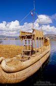 Travel photography:Uros boat docked at one of the floating reed islands in Lake Titikaka, Peru