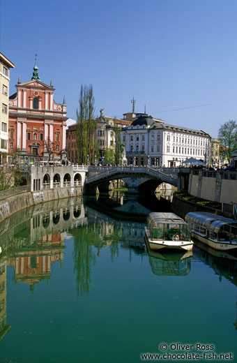 The Ljubljanica river in Ljubljana with the Franciscan church and Tromostovje (triple bridges) in the background