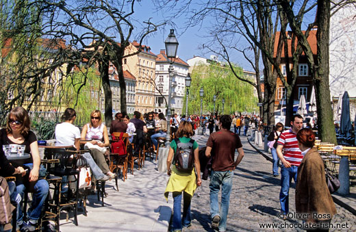 Street cafes with people along the river in Ljubljana