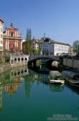 Travel photography:The Ljubljanica river in Ljubljana with the Franciscan church and Tromostovje (triple bridges) in the background, Slovenia