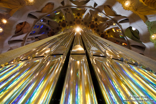 Colourful light from the stained glass windows is reflected off the organ pipes in the Sagrada Familia