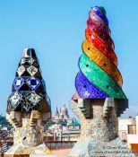 Travel photography:Sculpted chimneys on the roof of Palau Güell with MNAC in the background, Spain