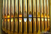 Travel photography:Colourful light from the stained glass windows is reflected off the organ pipes in the Sagrada Familia, Spain