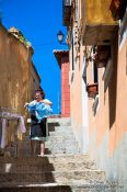 Travel photography:Toledo woman hanging clothes in street, Spain