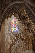 Travel photography:Sunlight enters through a coloured window into an ornate arabesque alcove of the Nazrin palace in the ranada Alhambra, Spain