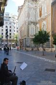 Travel photography:Busker outside the Palau del Marqués de Dosaigües in Valencia, Spain