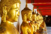 Travel photography:Row of golden Buddhas at Wat Pho temple in Bangkok, Thailand