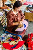 Travel photography:Woman painting a fan at the Bo Sang parasol factory, Thailand