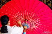 Travel photography:Adding the finishing touches to a large parasol at the Bo Sang parasol factory, Thailand