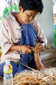 Travel photography:Woman cutting small pieces of wood at the Bo Sang parasol factory, Thailand