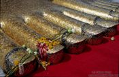 Travel photography:Toes of the Giant Buddha with flower offerings at Wat Intharawihan, Thailand