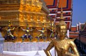 Travel photography:Golden Kinnara with demons Wat Phra Kaew in Bangkok, Thailand