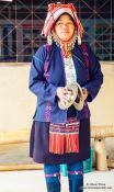 Travel photography:Woman in traditional dress perfoming a dance at the Ban Lorcha Akha village, Thailand