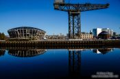 Travel photography:Glasgow River Clyde with disused dock crane and stadium, United Kingdom