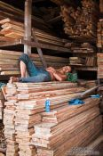 Travel photography:Man sleeping in a wood shop in Danang, Vietnam